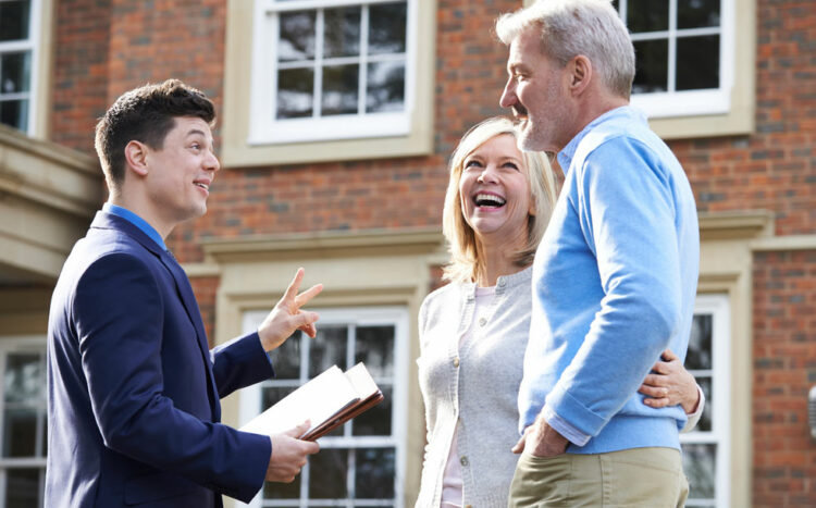 Real estate agents giving keys to the new owner
